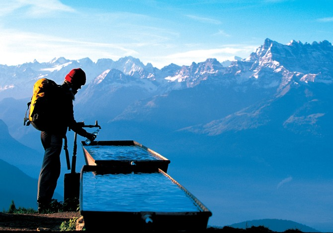 Brunnen Hiker at a rest stop at a fountain high above Leysin in the region of les Diablerets, Canton of Vaud. In the background the massif of Dents du Midi, 3178 m high. Swiss_Image_sts0433