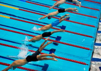 Tuffo dal blocco di partenza in piscinaTuffo dal blocco di partenza in piscina