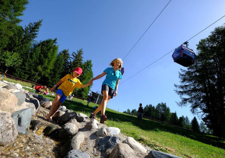 """In Val di Fiemme Trentino l'estate gioca d'anticipo e la stagione estiva entra nel vivo molto prima rispetto al passato. Sabato 29 maggio Bellamonte ha aperto la Cabinovia (fino a domenica 19 settembre, orario 9-12.45 - 14-17.15), le attività nella natura della Fiemme Guest Card sono iniziate già il 30 aprile e così il servizio Bike Express lungo la Ciclabile delle Dolomiti è attivo tutti i sabati e le domeniche dal 22 maggio al 6 giugno, per poi entrare in funzione ogni giorno. La cabinovia di Bellamonte Alpe Lusia già da un weekend riporta i bambini a divertirsi nel Giro D'Ali. Inoltre, domenica 13 giugno prenderà il via proprio a Bellamonte il nuovo """"Fiemme Trekking Gourmet"""" ideato dallo chef stellato Alessandro Gilmozzi. La passeggiata del gusto in discesa, di rifugio in chalet, coinvolge l'ApT Val di Fiemme, gli impianti di risalita di Predazzo, Pampeago e Alpe Cermis, con i ristoratori e i rifugisti della valle. Sabato 19 giugno al via gli impianti di Predazzo Latemar MontagnAnimata che resteranno aperti fino al 12 settembre (orari: Telecabina Predazzo-Gardoné 8.30-17.45; Seggiovia Gardoné-Passo Feudo 8.30-17.30). A Pampeago si raggiunge il Latemarium con la seggiovia Latemar da sabato 12 giugno fino a domenica 19 settembre, poi nei giorni 23, 24 e 30 settembre e 1 ottobre 2021 (orario: 8.30-13 e 14.15-17.30). La Seggiovia Agnello che porta parco RespirArt apre sabato 26 giugno e resta in funzione fino al 12 settembre (orario: 8.30-13.00 e 14.15-17.30). Gli impianti di risalita dell'Alpe Cermis partono sabato 26 giugno e restano attivi fino a domenica 19 settembre 2021 per raggiungere i rifugi, la ferrata, il Parco Avventura e Cermislandia (orari Cabinovie e Seggiovia Lagorai: 9.00-13.00 e 14.00-17.30). Seggiovie e cabinovie tornano quindi in movimento, dopo una lunga pausa, interpretando il desiderio collettivo di spazio e movimento, nel rispetto delle norme anti-Covid19, quindi in sicurezza."""